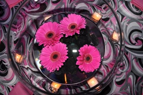 For this centerpiece, just add black, smooth stones (you can find them anywhere from Z Gallerie to World Market to your local craft store) to the bottom of the vase, enough to reach just about two inches high. Next, fill the vase with water to about four inches above the rocks. Then, snip the tops off of four fabulous hot pink Gerber daisies, and let them float on top of the water!
