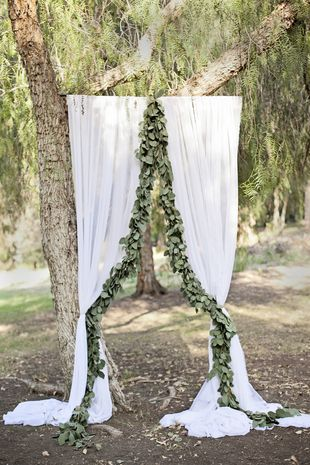 Wedding ceremony arch with light, airy white fabric and silver dollar eucalyptus garlands {Nicolette Moku Photography}: