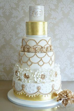 A stunning cake with different designs to each tier with real gold leaf and Indian style elements. Display on a base of beautiful cream roses for the ultimate Wedding centrepiece.