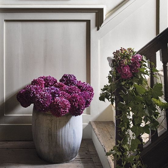Gather lengths of trailing ivy and berries, tie them together in a generous bundle and fix it to the banister at the bottom of the stairs. Build the effect with a second arrangement nearby; we simply filled a large industrial-style container with glorious hydrangeas. Homes & Gardens. http://www.hglivingbeautifully.com/2015/12/02/make-an-entrance-ideas-for-decorating-your-hallway-this-christmas/