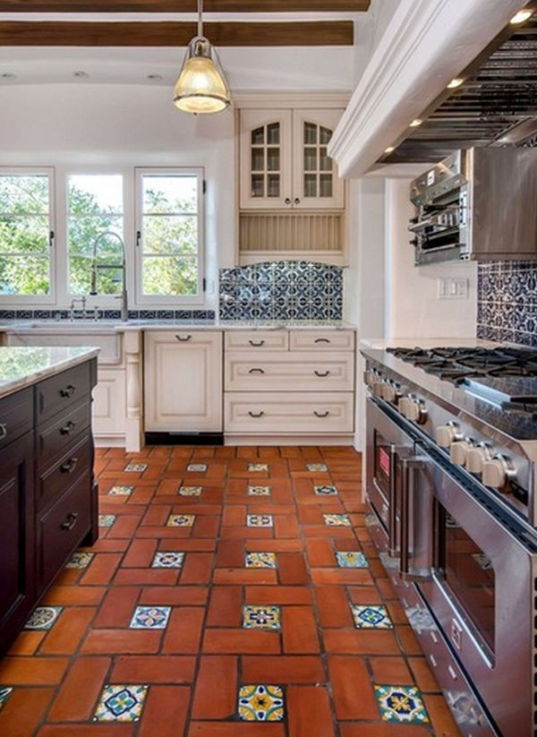 Spanish Style kitchen features 3 light windows, terracotta floor with glazed accent inserts, blue/white backsplash tiles, off white cabinets with arch upper detail.