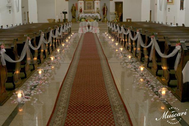 dekoracja ślubna w kościele - tiul na ławkach i świece i płatki kwiatów