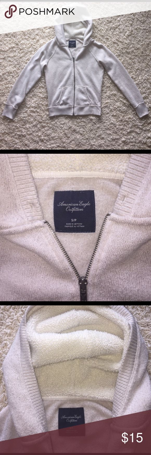 AE 🦅 Zip Up Hoodie Light beige women's zip up hoody from American Eagle. Super comfy. Thicker than your average zip up hoodie so it is pretty warm. Hood is warm and fuzzy as shown in picture. There is pilling as shown in pictures as well. Missing hoody tie. Otherwise in good condition! American Eagle Outfitters Sweaters