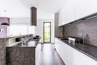 Kuchyň má výhled do zahrady. Neutrální bílou sestavu si majitelka navrhla sama a nechala na míru zhotovit u místní firmy Interiéry Volf.