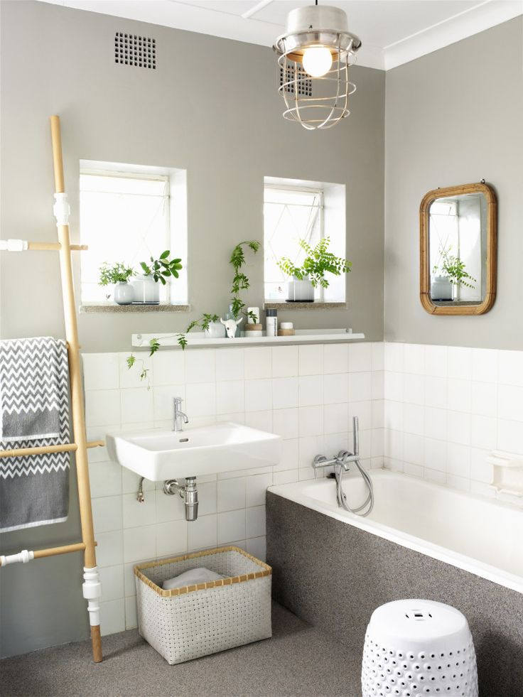 Renovated bathroom - sink and bathtub against half-height tiled wall below walls painted pale grey