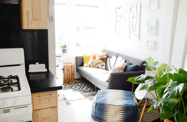 A bright and cozy living room area is where the roommates can watch TV or enjoy the views of their Oceanview neighborhood. The small futon is from Overstock, and the nude woman painting is by ZVNNI.