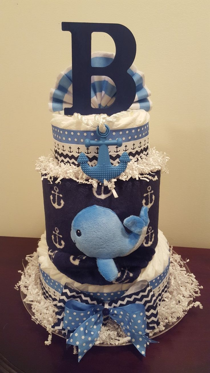 Nautical baby shower centerpiece gift. Diaper cake includes navy anchor blanket, whale blanket toy, anchor teether, initial letter, 3 small flannel burp cloths, 60 Pampers swaddlers. Visit my Facebook page Simply Showers for more pics and orders. Thanks Kim