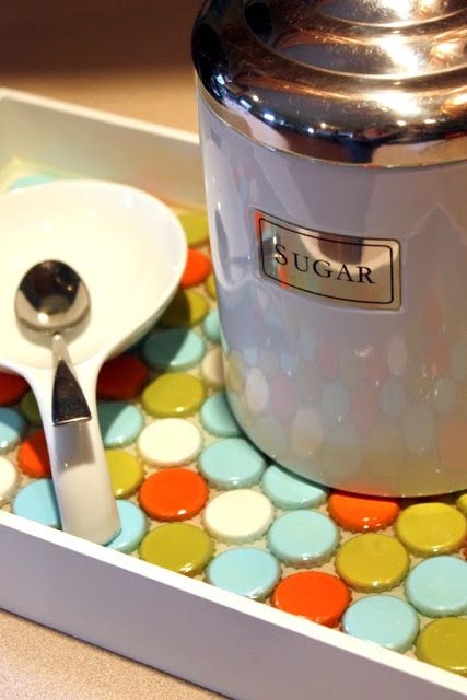 """Spray painted bottle caps, paint a tray white, arrange dry caps on dried tray, next used """"acrylic water"""" to pour over the caps. 2 part epoxy is sold at HL & Michael's, but it is cheapest at Walmart, in Floral Dept. Follow the directions, mix the compounds and pour it on. It's self-leveling. Wait 48 hours, it cannot be disturbed at all! The acrylic hardens & is ready for use! So cute! Also use buttons, pennies or peppermints for Christmas."""