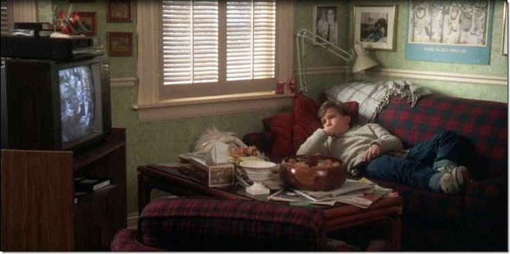 The upstairs TV room, where we see Rusty (a very young Johnny Galecki of Roseanne & The Big Bang Theory) watching It's A Wonderful Life, is filled with a comfortable plaid couch and chair for lounging in, while an understated damask wallpaper acts as a background for family photos and mementos #ThrowbackThursday #TBT #decor #holiday #Christmas