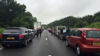 """Image copyright                  PA                  Image caption                     Organisers said current wet weather and ground conditions were causing delays   Glastonbury festival-goers have been stuck in queues of up to 12 hours as traffic chaos hits all major routes to the site. Organisers said rain and ground conditions had caused delays and urged people """"not to set off"""".  Festival founder Michael Eavis apologised and said: """"We"""