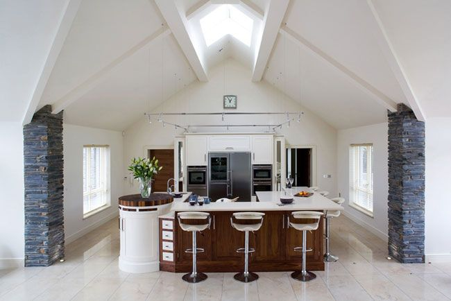 Located in the united kingdom this open plan white kitchen features pillars covered in blue for Modern open plan house designs ireland
