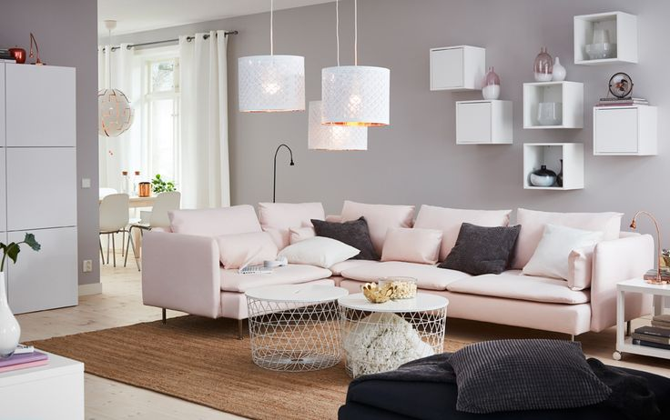 A medium-sized living room furnished with a large corner sofa in a light pink cover shown together with two white storage tables and  six small wall cabinets, three with doors and three without.
