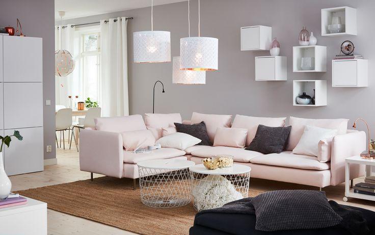 Salón mediano con un sofá esquinero grande con funda en rosa claro, dos mesas blancas con compartimentos, y seis armarios de pared pequeños (tres con puertas y tres sin puertas).