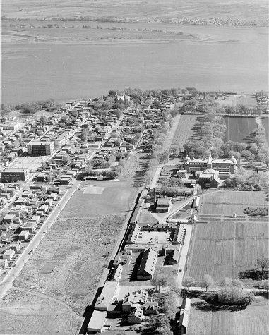 Vue aérienne de l'ancien village de la Longue-Pointe, qui sera démoli pour la construction du pont-tunnel Hippolyte-La Fontaine (environ 1963). À droite, les terrains et installations de l'hôpital Saint-Jean-de-Dieu, anciennement hôpital Louis-H. Lafontaine, aujourd'hui l'Institut universitaire en santé mentale de Montréal. (Collection Ministère des transports du Québec)