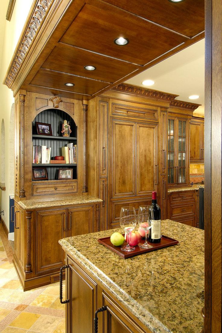 Recessed lighting brings tons of light into this Mediterranean kitchen boasting dark wood cabinets and paneling. Neutral, stone tile floors balance and brighten the masculine, dark tones that surround the exquisite space.