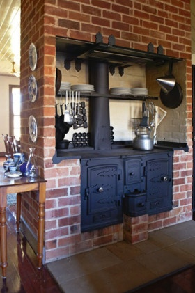 nice colonial style house, here: kitchen. If I could learn to cook on a woodstove, this would be terrific!! Could it be set up (as it looks here) so that some of the heat warms the other room?