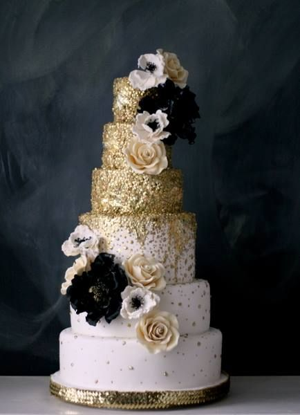 gold wedding cake with black floral accents