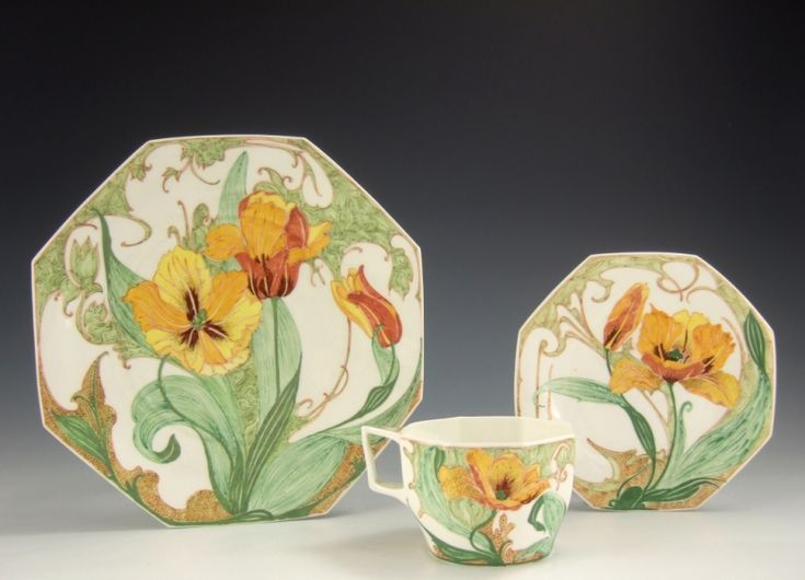 Een eierschaalporseleinen déjeuner set met een achtkantige kop, schotel en groot bord, beschilderd met rood-geel-oranje tulpen. Het kopje (model 225) is 5½ cm hoog, diameter van het schoteltje (model 14) is 14½ cm en de diameter van het bord (model 15) is 21cm. Werkordernummers 245 en 216, gemerkt met het jaarmerk 1914, het monogram van Sam Schellink en het geschilderde fabrieksmerk
