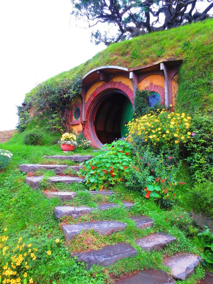 Hobbit House, New Zealand. I've always loved the hobbit hole houses which were inspired by a house in great britain that was cut out of the side of a stone hill