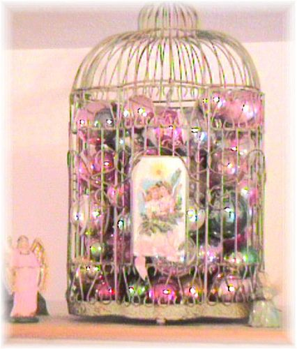 Fill an old birdcage with pretty ornaments and place a Christmas card on the outside.  I think adding a small string of lights would be beautiful at night, too.