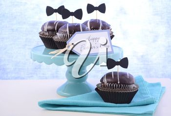 Happy Fathers Day cupcakes on cake stand against a blue background.