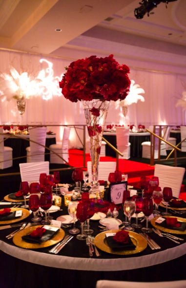 Love the white centerpieces that perfectly contact with the red.  Feathers add whimsy and grandeur.