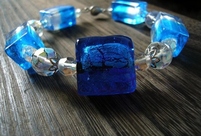 Priam ľadový náramok pozostáva zo stredovej vinutky so striebrom v tele, dvojfarebné modro-biele vinutky, brúsené sklo-ohňovky dvoch veľkostí v čírom odtieni s pokovom-trblietavý efekt!  Veľké ohňovky su okrášlené kovovými kaplíkami, navlečené na pamäťovom drôťe s elegantným zapínaním.