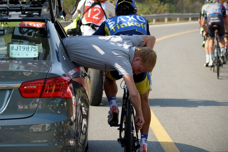 A staff of team Saxo Tinkoff repairs the bicycle for a cyclist as they ride through a country road during the first stage of the 2013 Tour of Beijing cycling race in China.