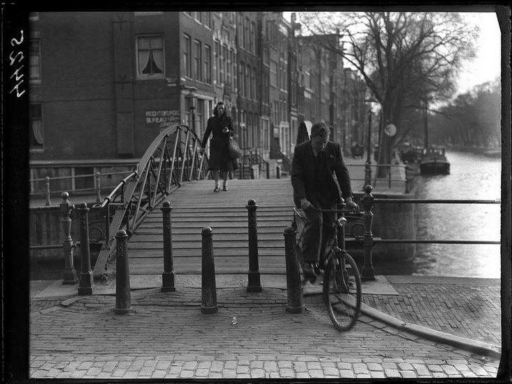 Ondanks dat de afrit van de Melkmeisjesbrug (brug 16) is volgezet met paaltjes komt een fietser er toch nog langs, hoek Herengracht en Brouwersgracht, Amsterdam, april 1948 Foto Ben van Meerendonk