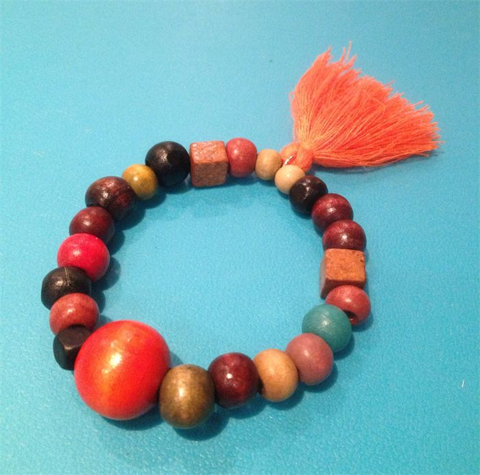 Warm toned beaded bracelet with orange tassel