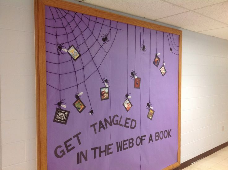 School #library ideas, bulletin boards and displays, #Halloween #October bulletin board. Spiders cut out of construction paper and the web is made with yarn. Books in the web are all about spiders some fiction and nonfiction.