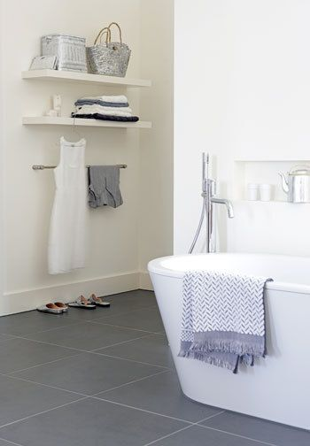 <3 slate floor tiles in white bathroom. Love the bath and the shelving.