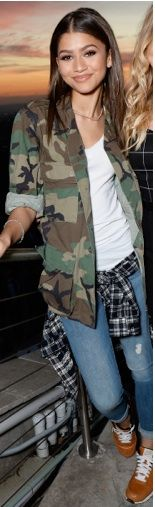 Zendaya wearing sneakers and a camo jacket with a plaid shirt tied around her waist