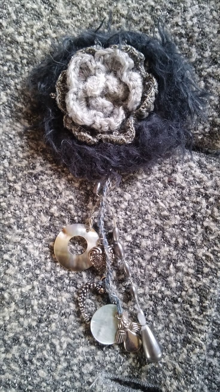 free form brooch 2: Scrap yarn incl. tiny glass seed beads, shell charms, metal charm, drop shape pearl etc.  Adorns  my old grey tweed jacket!