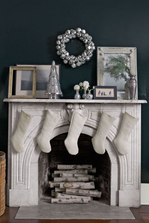 A jingle-bell wreath and mercury-glass tree dress up the marble mantel of this Connecticut farmhouse.