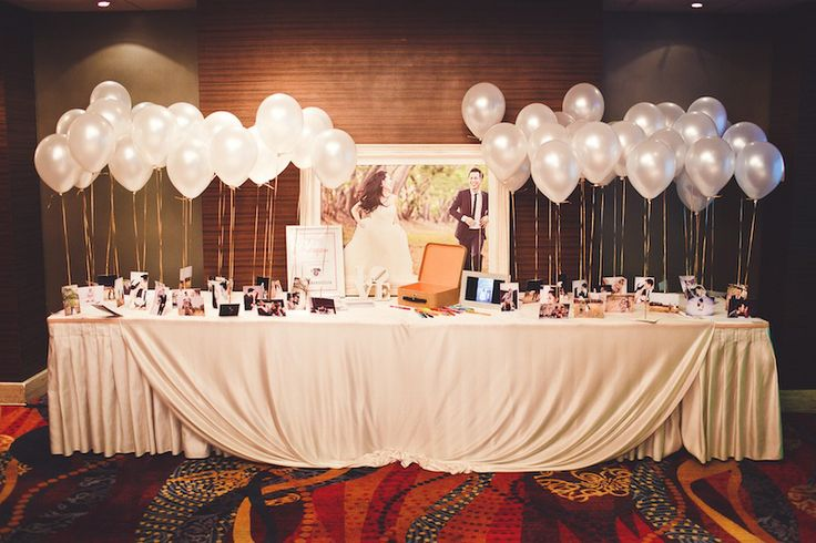 The couple's reception table was decorated with balloons. To every balloon was tied a photograph from their engagement shoot.