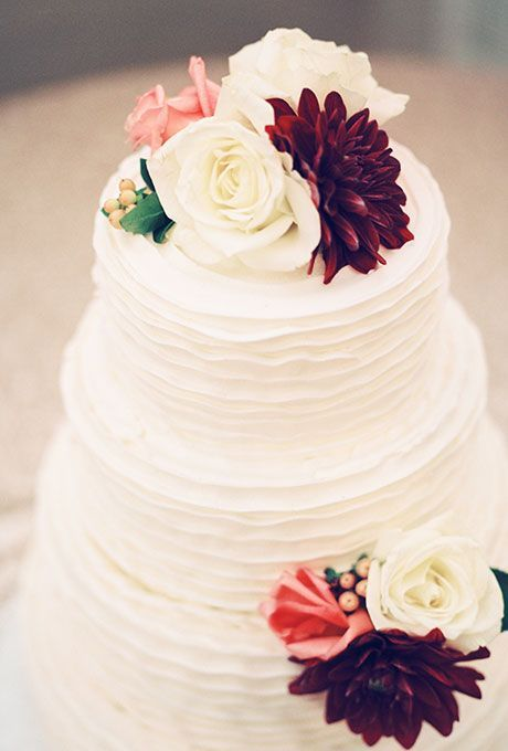 Brides: Classic White Cake with Autumnal Flowers. A three-tiered textured wedding cake decorated with white roses, burgundy dahlias, and berries, created by Simply Decadent Bakery.