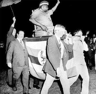 Avec un certain sens de la mise en scène, Idi Amin Dada se fait porter par quatre britanniques lors du sommet de l'OUA