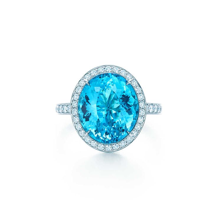 Tiffany & Co. -  Esteemed Blue CuprianElbaite Tourmaline Ring: A ring of white diamonds frames a blue cuprian elbaite tourmaline of esteemed origin set in platinum. Carat weight: blue tourmaline, 5.47. Carat total weight: round brilliant diamonds, 1.02; princess-cut diamonds, .36.