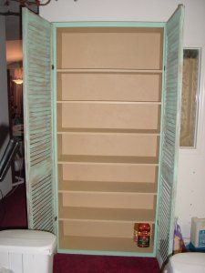 old pair of shutter doors attached to a basic bookshelf with trim around the outside to attach the shutters to.