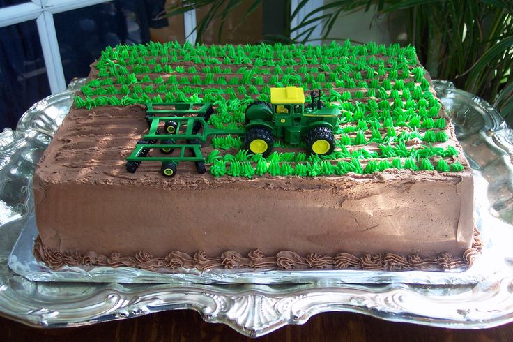 This chocolate cake has rows of crops that a John Deere Tractor is plowing. All in a days work for this groom.