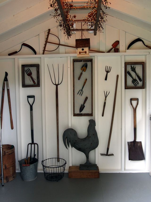 rusty garden tool farm themed wall gallery on white planked walls