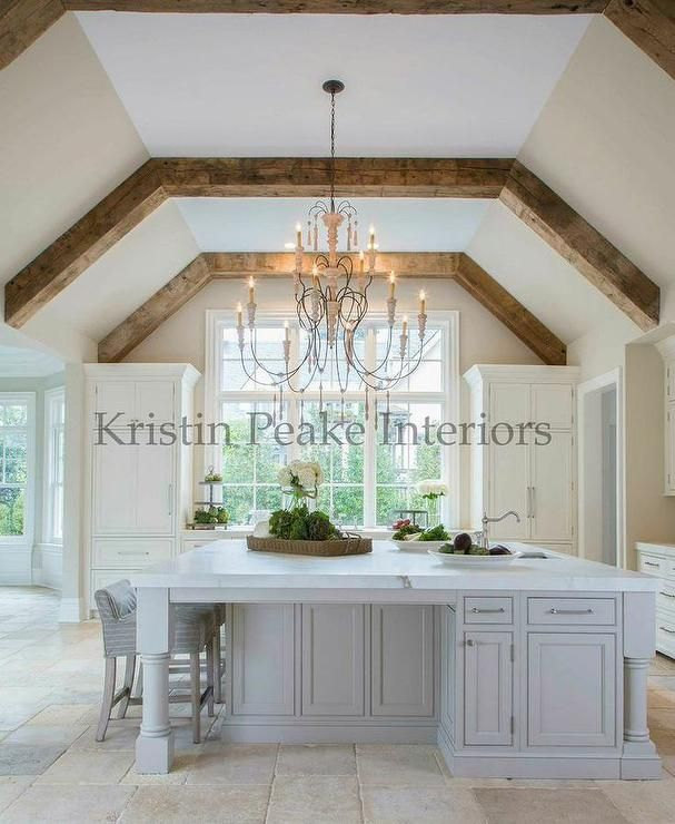 Elegant kitchen with vaulted ceilings lined with rustic wood beams accented with a French candle chandelier illuminating an oversized French grey island topped with white marble.