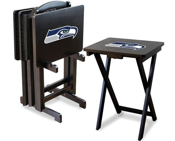 [[start tab]] Description Show your team spirit by having the Seahawks team logo displayed proudly on these Seattle Seahawks NFL TV Trays. This is sold as a set of four snack trays with a storage rack