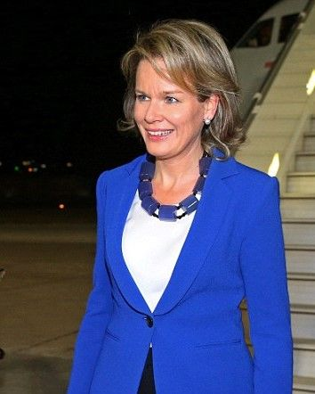 Queen Mathilde of Belgium stepped off the plane wearing a blue jacket and black trousers, adding a statement beaded necklace to her ensemble as she arrives in Jordan on 23 October 2016
