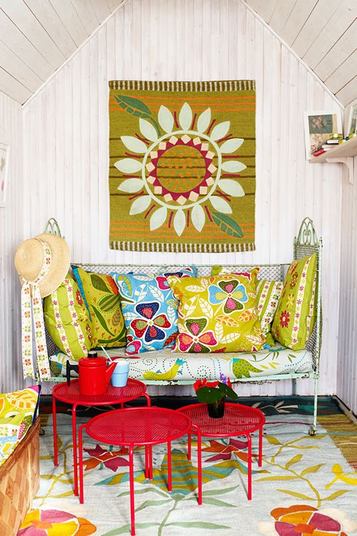 Just adorable...fun colors, fabulous pillows, and loads of charm! I will have my coffee here...when it rains!