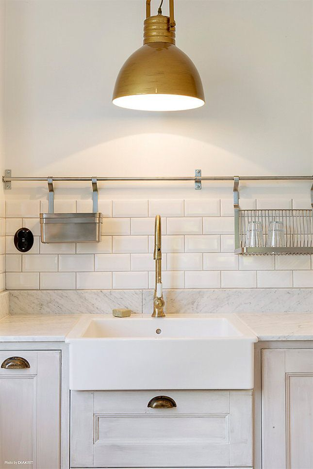 Brass fixtures, farmhouse sink, subway tiles, marble countertops, brass bar for hanging kitchen utensils and such