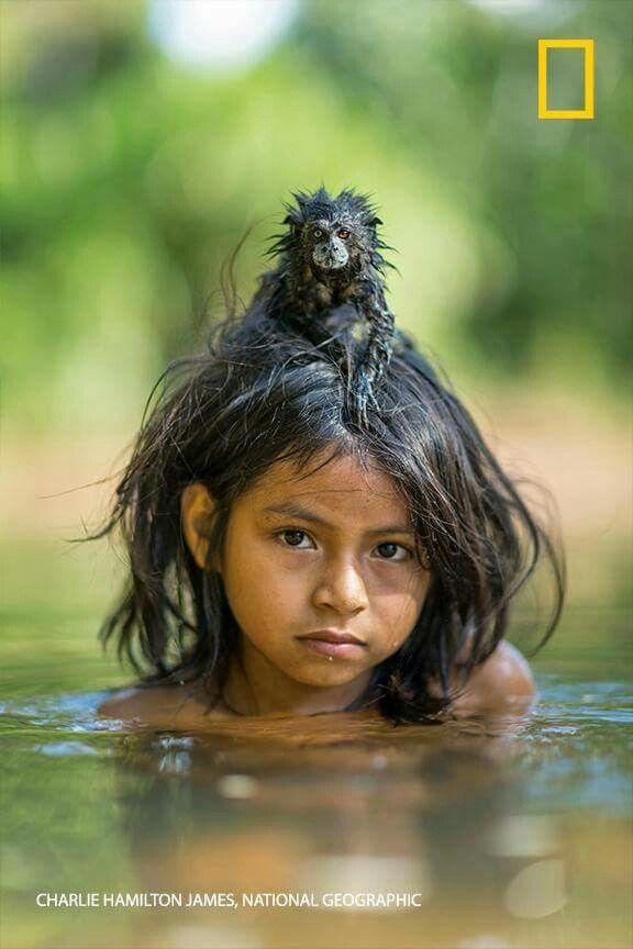Yoina, a member of the Matsigenka tribe that lives deep inside Peru's Manú National Park, swims in the Yomibato River with her pet saddleback tamarin. Read the full story: http://on.natgeo.com/1UjIG20