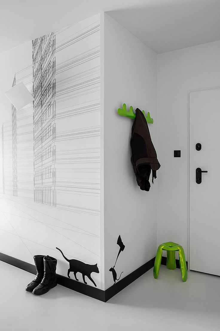Black and white wall decals and bright pops of green welcome you at the entrance of the apartment Small Black And White Apartment In Poland Exudes Refined Minimalism