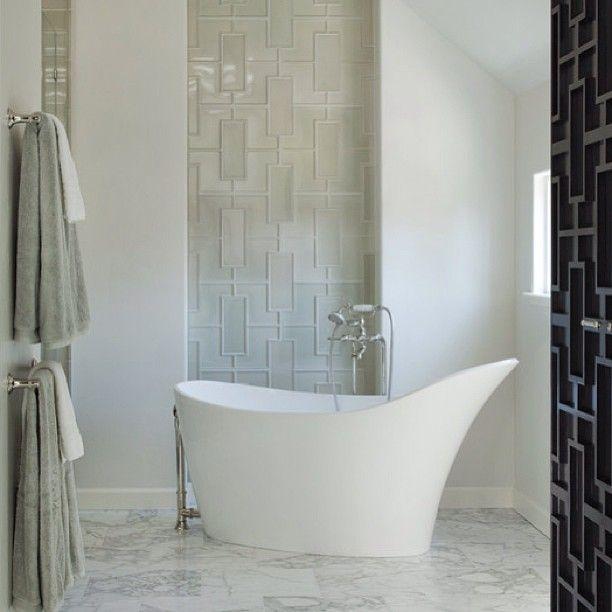 A humongous teapot-shaped bathtub takes center stage on this white minimalist bathroom #dreambathroom